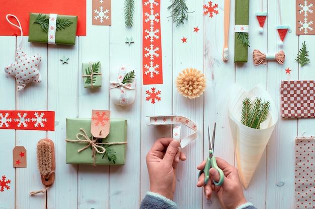 Várias decorações naturais de férias de inverno de natal ou ano novo, pacotes de papel ofício e presentes ecológicos zero resíduos. postura plana em madeira, mãos cortando a fita para decorar o cone de madeira ..