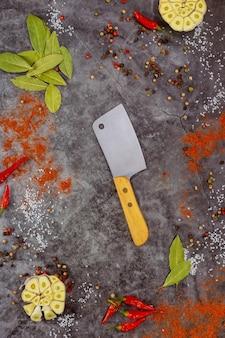 Várias ervas e especiarias com faca e alho.