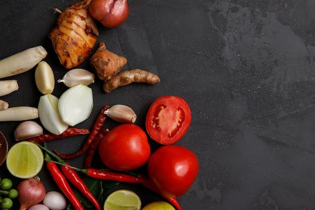 Várias ervas e ingredientes para cozinhar em fundo escuro.