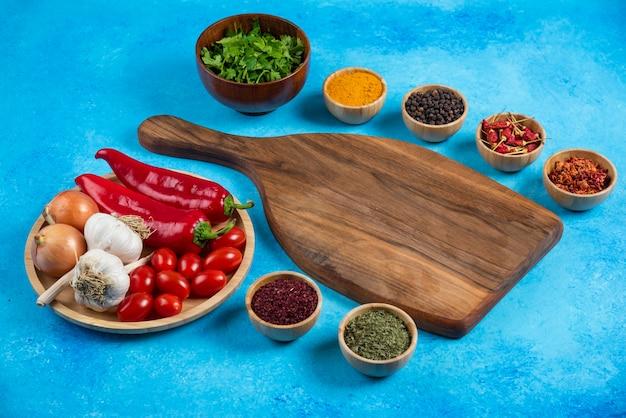 Várias especiarias ao redor da placa de madeira com prato de legumes.