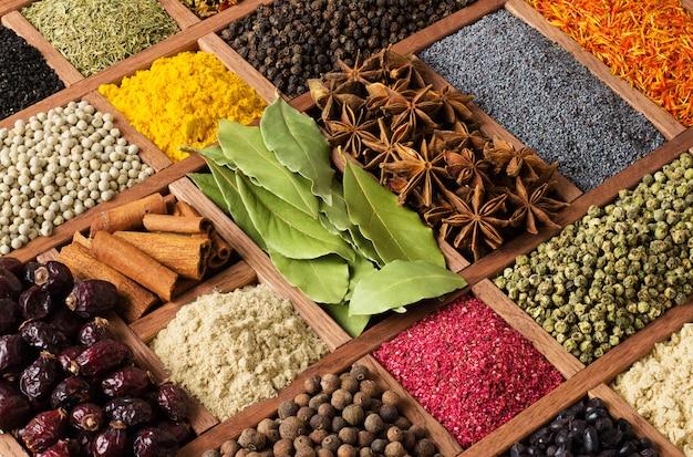 Várias especiarias em caixa de madeira, vista superior. condimentos para cozinhar alimentos como pano de fundo.