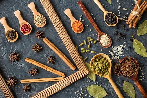 Várias especiarias em colheres de madeira na mesa de pedra escura