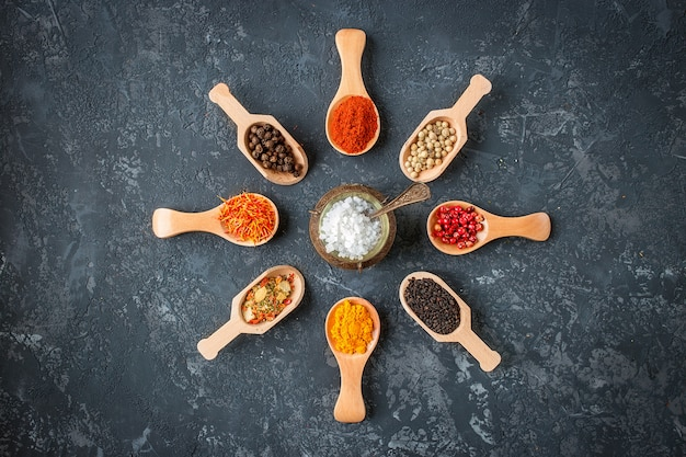 Várias especiarias indianas em colheres de madeira, sementes, ervas na mesa de pedra escura. especiarias coloridas, vista superior. alimentos orgânicos, estilo de vida saudável, espaço para texto
