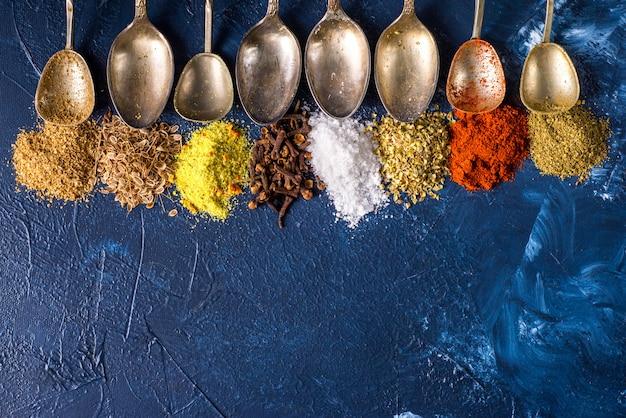 Várias especiarias moída açafrão pimenta gengibre canela erva tempero sal páprica cominho sementes vintage colher em cima da mesa. vista de cima. especiarias indianas