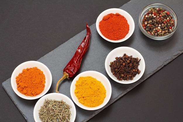 Várias especiarias moídas coloridas, açafrão, cominho, curry, alecrim seco, cravo e frutas da pimenta da jamaica em tigelas de porcelana em uma tábua de pedra preta com pimenta vermelha seca. vista do topo.