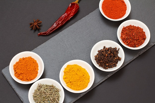 Várias especiarias moídas coloridas, açafrão, cominho, curry, alecrim seco e cravo em tigelas de porcelana em uma tábua de corte de pedra preta com pimenta vermelha seca. vista do topo.