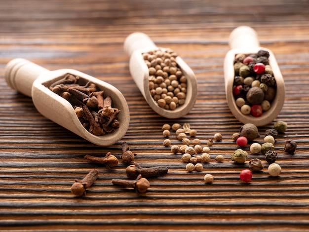 Várias especiarias numa superfície de madeira. cravinho, sementes de coentro e pimentos em colheres de pau. nitidez selecionada. macrofotografia