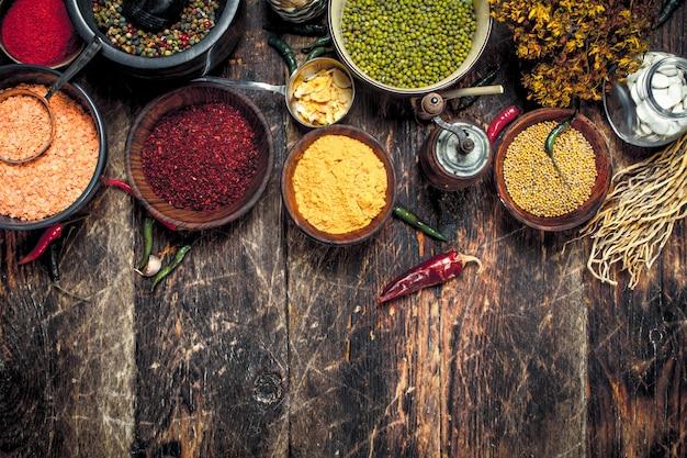 Várias especiarias perfumadas e ervas na mesa de madeira.