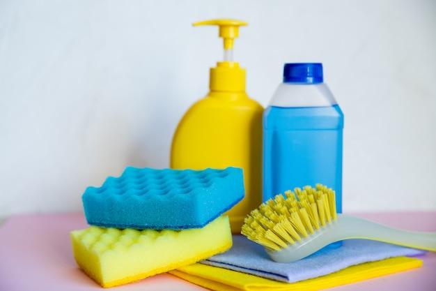 Várias esponjas e garrafas plásticas com produtos de limpeza
