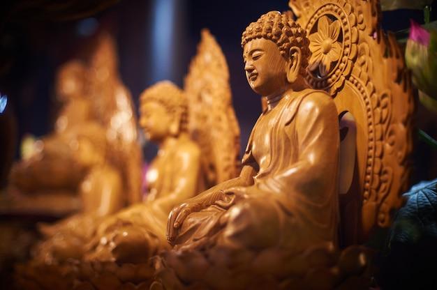 Várias estátuas de buda esculpidas em madeira no templo budista