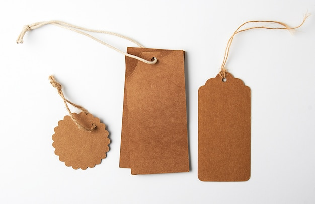 Várias etiquetas de papel pardo com cordas no fundo branco