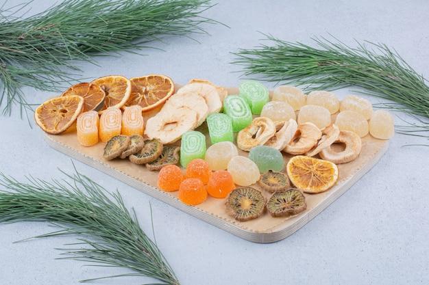 Várias fatias de frutas e doces de geleia na placa de madeira.