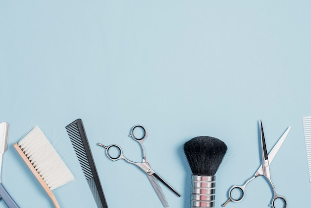Várias ferramentas de barbeiro, dispostas em uma linha em fundo azul
