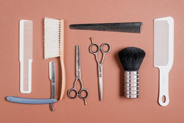 Várias ferramentas de barbeiro em pano de fundo marrom