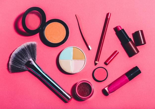 Várias ferramentas de beleza em um fundo rosa
