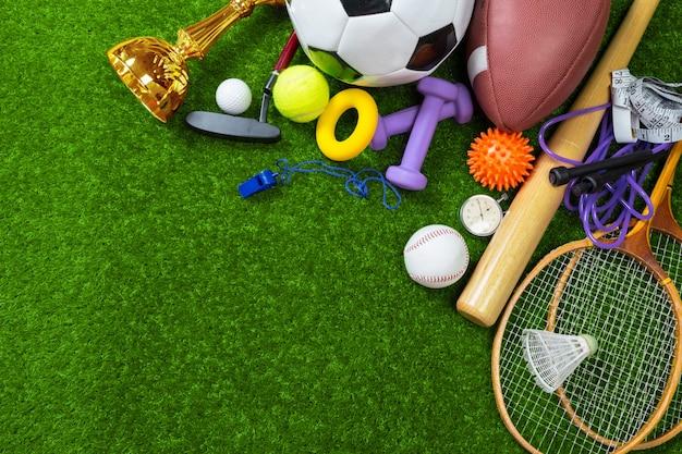 Várias ferramentas de esporte e bolas na grama, vista superior de fundo