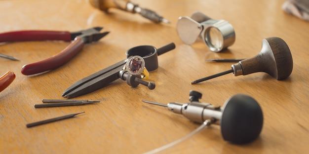 Várias ferramentas de joalheiro na mesa de madeira