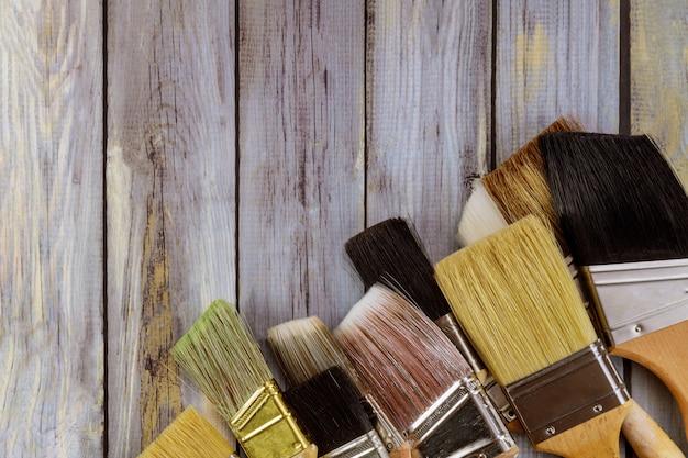 Várias ferramentas de pintura escovam no fundo da mesa de madeira branca