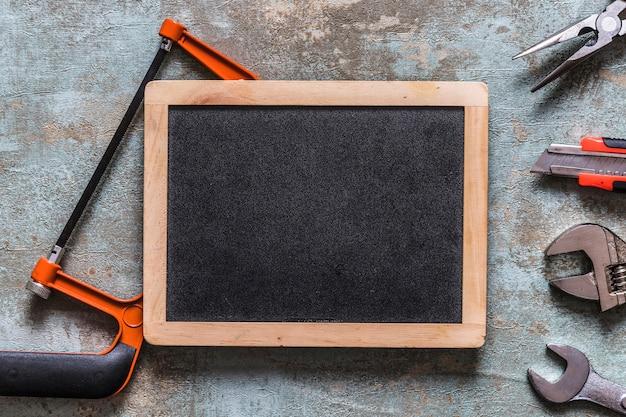Várias ferramentas de trabalho e ardósia em branco na velha mesa de madeira