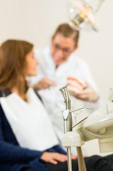 Várias ferramentas de um dentista esperando para ser utilizado na cirurgia, no a entdentist está dando tratamento a uma paciente do sexo feminino