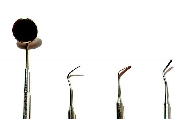 Várias ferramentas dentárias dispostas flatlay sobre um fundo claro