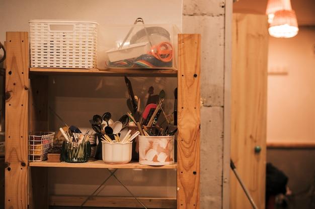 Várias ferramentas e colheres no suporte na prateleira de madeira