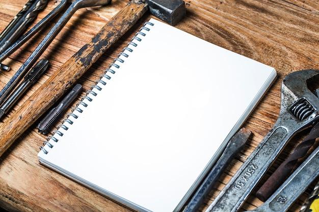 Várias ferramentas e o caderno em branco em um fundo de madeira