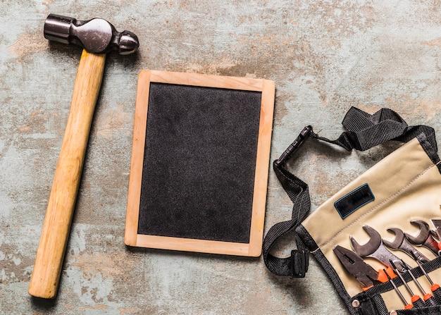 Várias ferramentas em toolbag perto de ardósia e martelo na mesa de madeira enferrujada