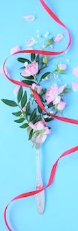 Várias flores delicadas em uma colher com fita vermelha sobre fundo azul. conceito de bebida aromática