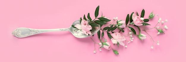 Várias flores delicadas em uma colher em um fundo rosa. conceito de bebida aromática