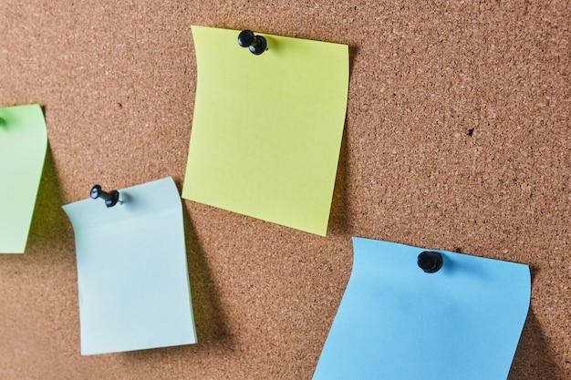 Várias folhas de anotações coloridas fixadas no quadro de cortiça, foco seletivo, espaço de cópia