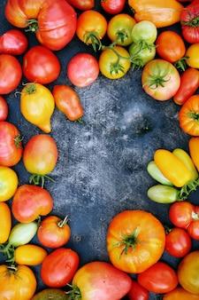 Várias formas e cores de tomates em um fundo escuro