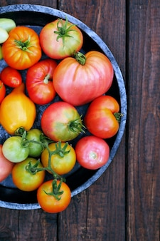 Várias formas e cores de tomates em uma placa de metal