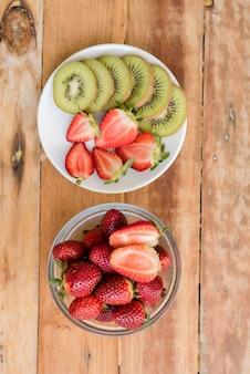 Várias frutas com vegetais no fundo de madeira