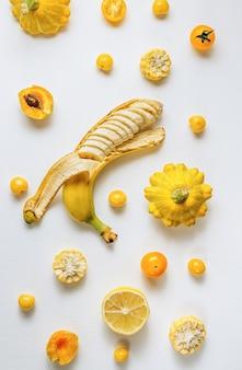 Várias frutas e vegetais de cor amarela e laranja no fundo da mesa branca. layout de alimentos. dieta colorida. conceito de comida vegana saudável.