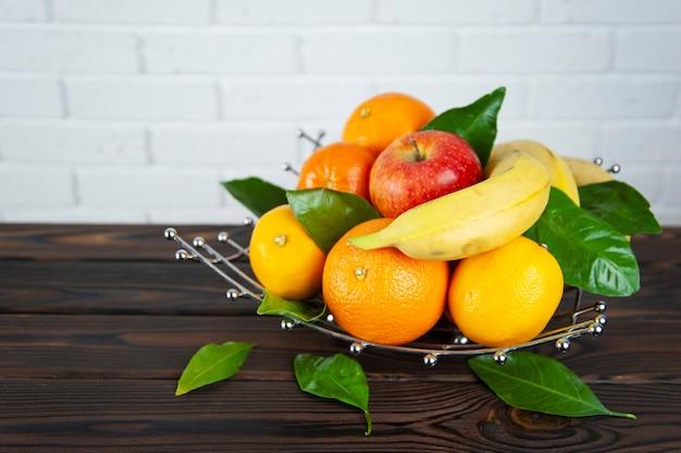 Várias frutas em uma fruteira de metal sobre uma superfície de madeira