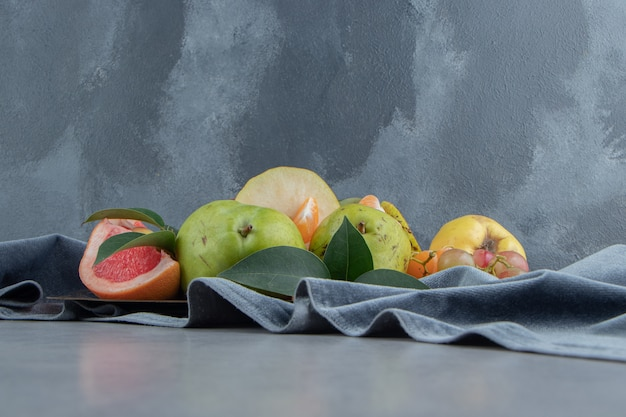 Várias frutas empacotadas em um pedaço de tecido sobre mármore