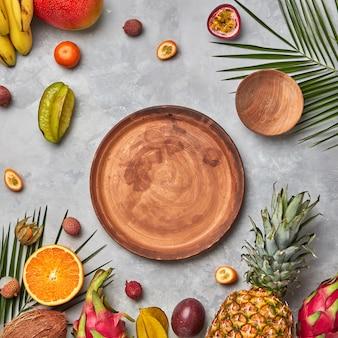 Várias frutas exóticas suculentas, coco, lichia, carambola, abacaxi, folhas de palmeira e placas de madeira marrons vazias em uma mesa de concreto cinza
