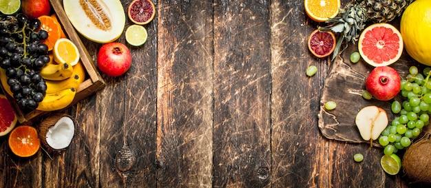 Várias frutas maduras em uma caixa de madeira. em uma mesa de madeira.