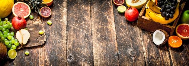 Várias frutas maduras em uma caixa de madeira na mesa de madeira.