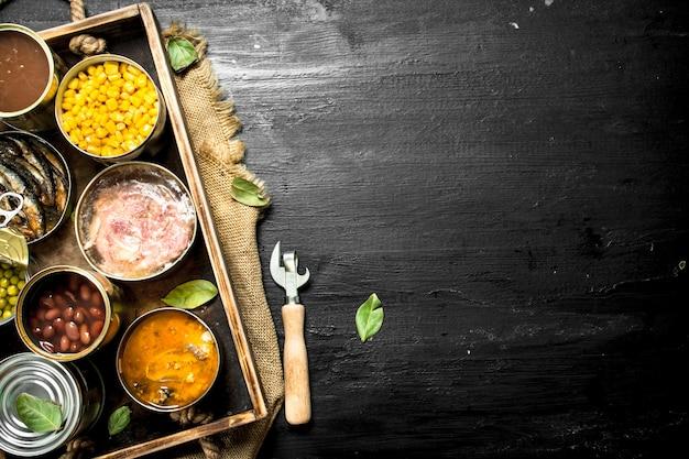 Várias frutas, vegetais, peixes e carnes enlatados em latas na velha bandeja no quadro negro