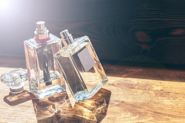 Várias garrafas com perfume em raios de sol na mesa de madeira
