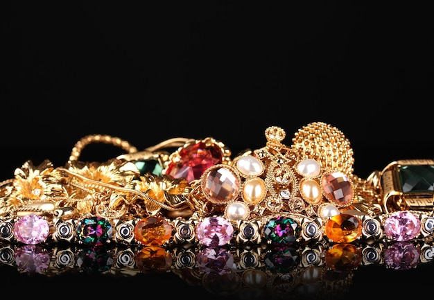 Várias joias de ouro na mesa preta