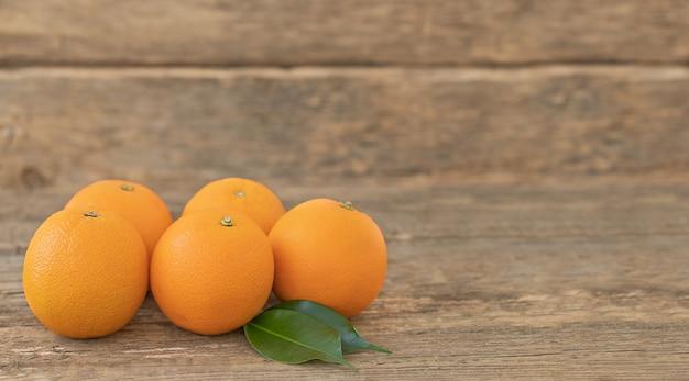 Várias laranjas inteiras com folhas verdes em uma mesa de madeira