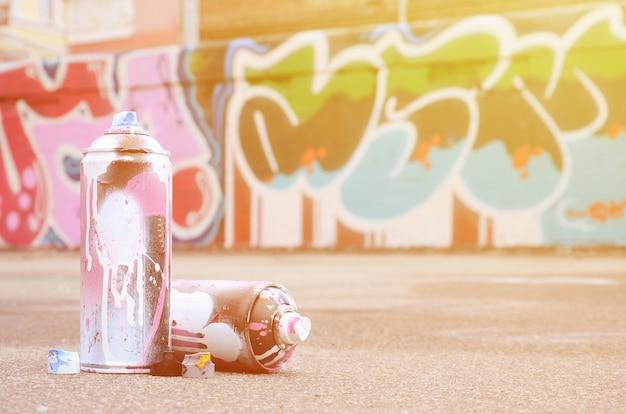 Várias latas de spray usadas com tinta rosa e branca perto da parede pintada em desenhos coloridos de grafite