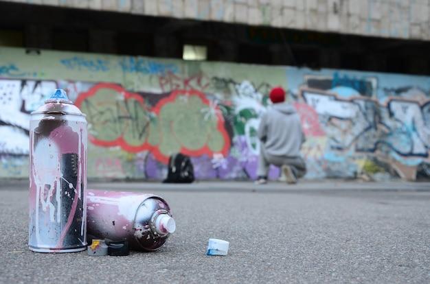 Várias latas de spray usado com tinta rosa e branca encontram-se no asfalto contra o cara em pé