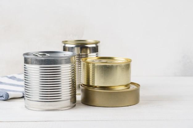Várias latas fechadas com conservas alimentares sobre uma mesa cinza clara. conceito de comida enlatada. doações de alimentos. copie o espaço.