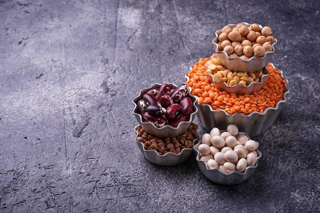 Várias leguminosas. grão de bico, lentilhas vermelhas, lentilhas pretas, ervilhas amarelas e feijões. foco seletivo