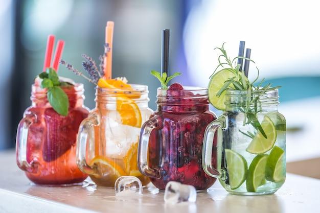 Várias limonadas em potes de vidro com laranja lima, limão, morangos otange e frutas frescas.