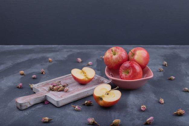 Várias maçãs no prato com rosa murcha no escuro.